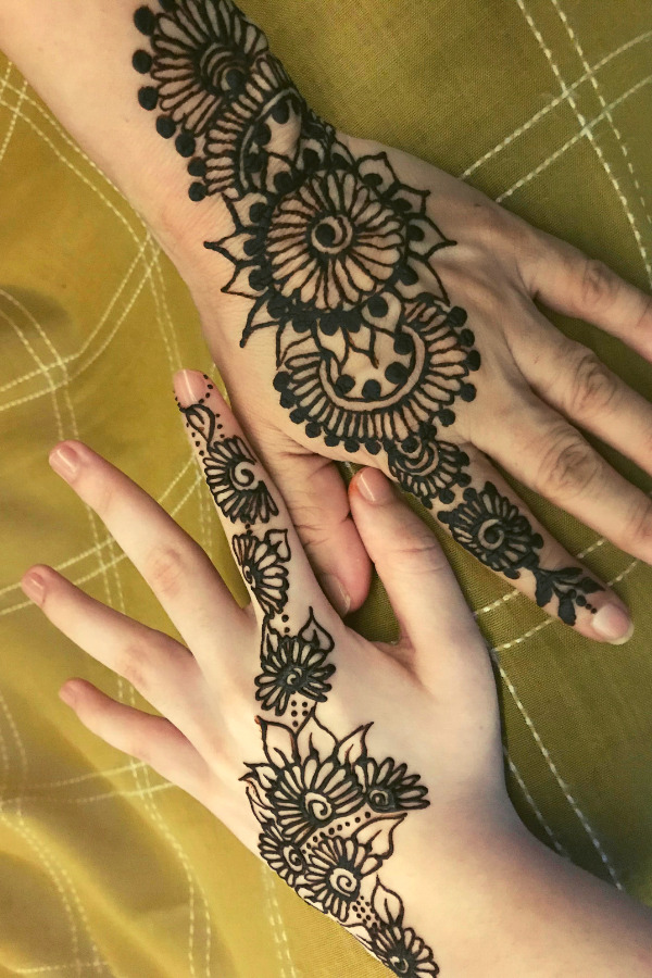 Two hands with floral Mehendi patterns applied placed across from each other on a checkered background