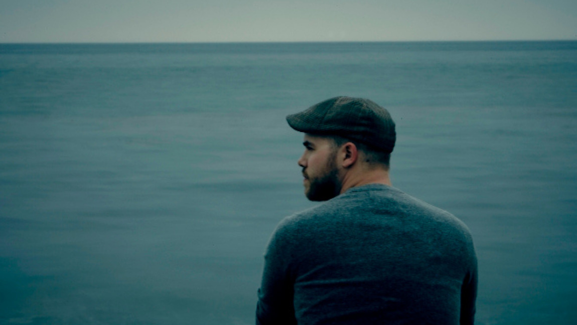 A photo of Ryan O'Neal, leader of the band Sleeping at Last, sitting by the ocean.