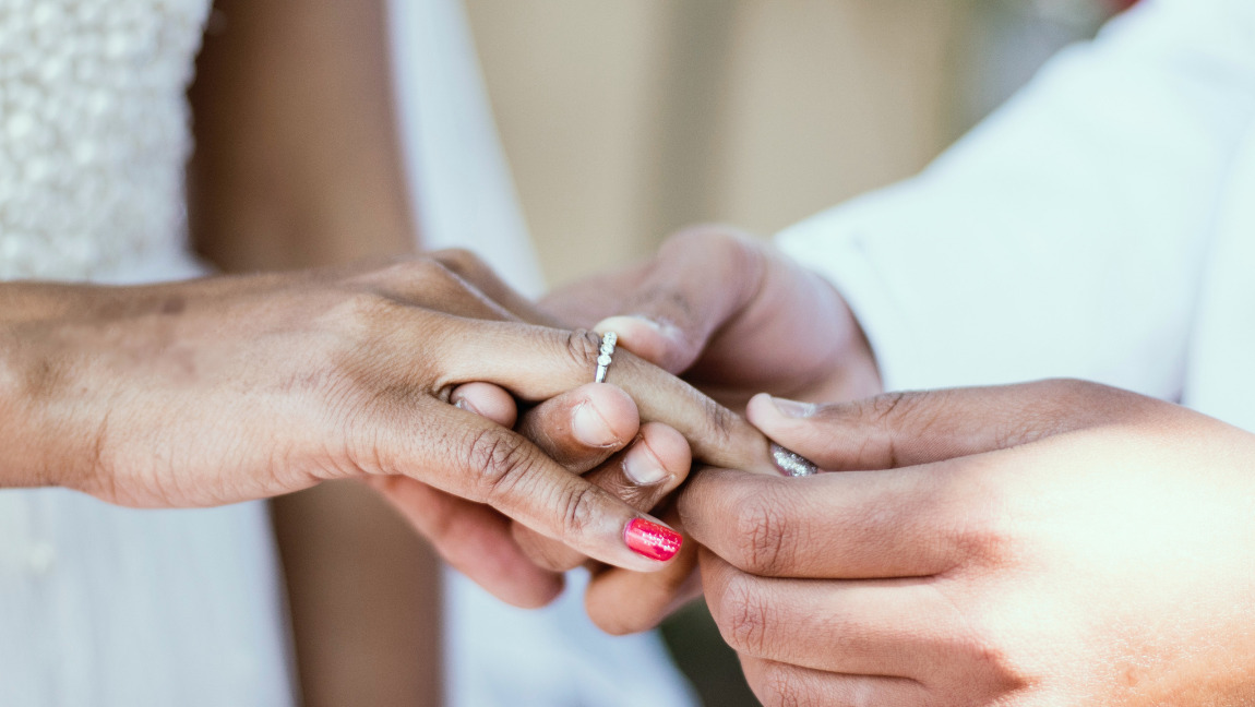 [image description: man putting ring on woman's finger] Via Unsplash