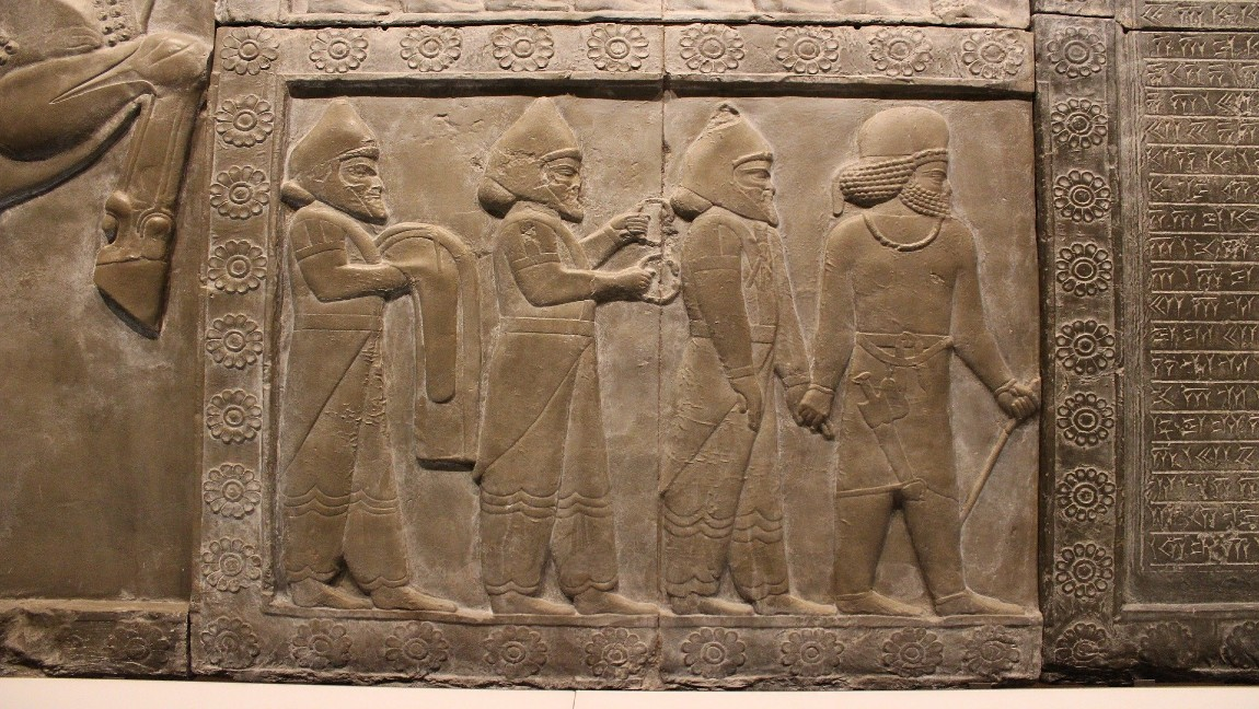 [image description: tablet with engraving of four men standing]