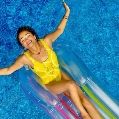 A woman in a yellow swimsuit relaxing on a floaty.