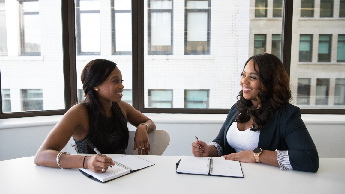 Two women sit smiling at a table with notebooks open in front of them