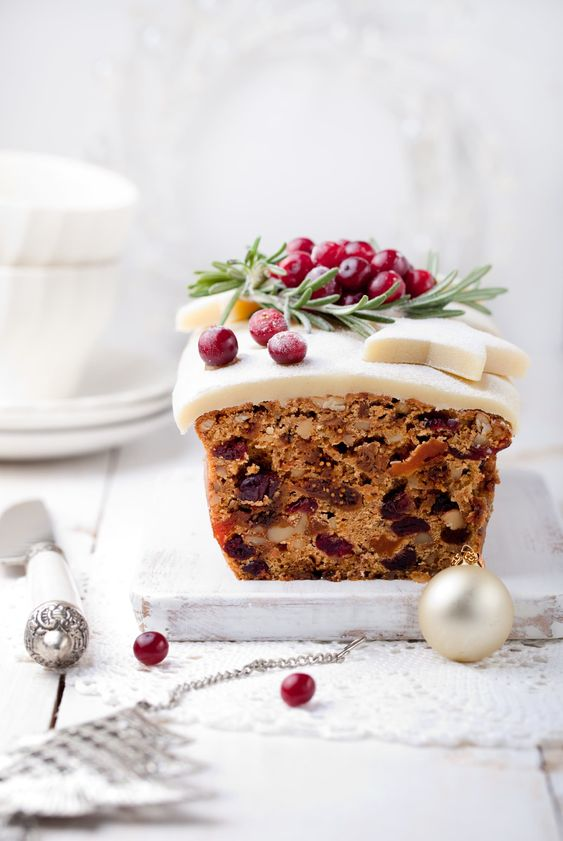 [Image description: a slice of iced fruitcake decorated with cherries Via Pinterest