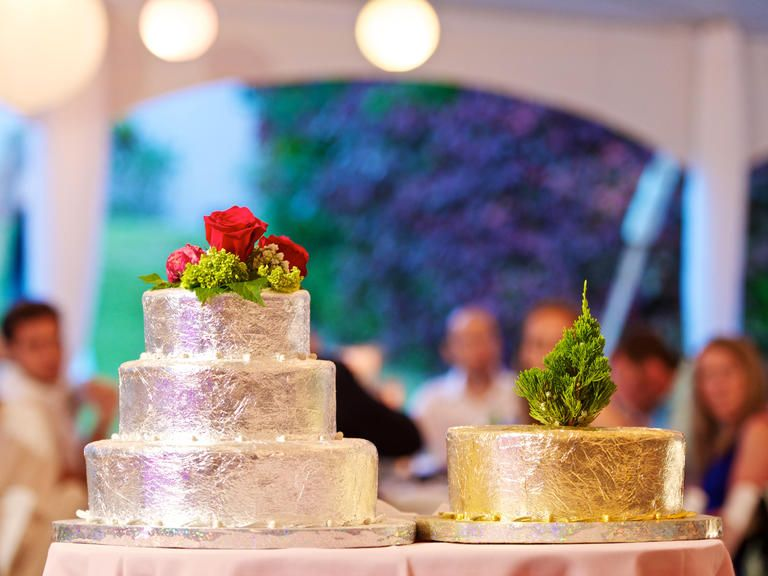 [Image description: two cakes on a table. One is a three tiered silver leaf cake topped with roses and the other is a one tiered cake covered in gold leaf] Via Pinterest