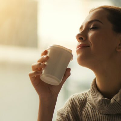 [Image description: Woman about to drink from plastic cup.] Via Pexels