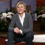 A photo of Ellen DeGeneres smiling and sitting on a stage.