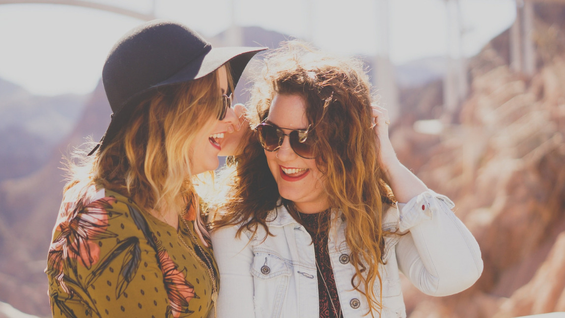 Two women laugh together.