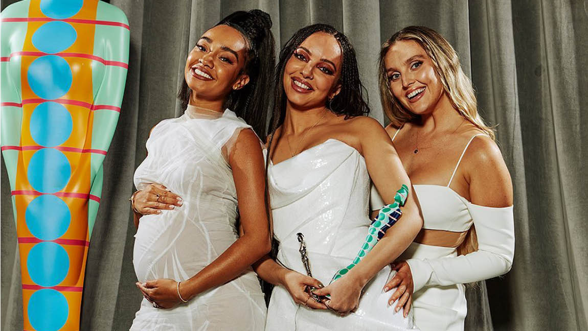 [Image Description: (left to right) Leigh-Anne Pinnock, Jade Thirlwall and Perrie Edwards of Little Mix standing in their white gowns with their BRIT Award for Best British Group.]