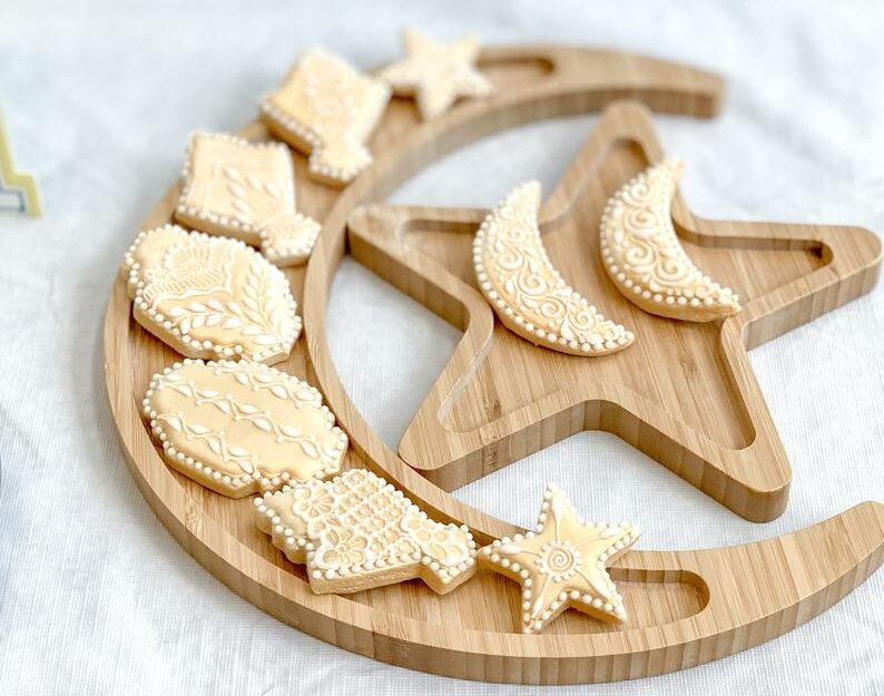 [Image Description: a wooden serving tray in the shape of a crescent moon and star] via Etsy