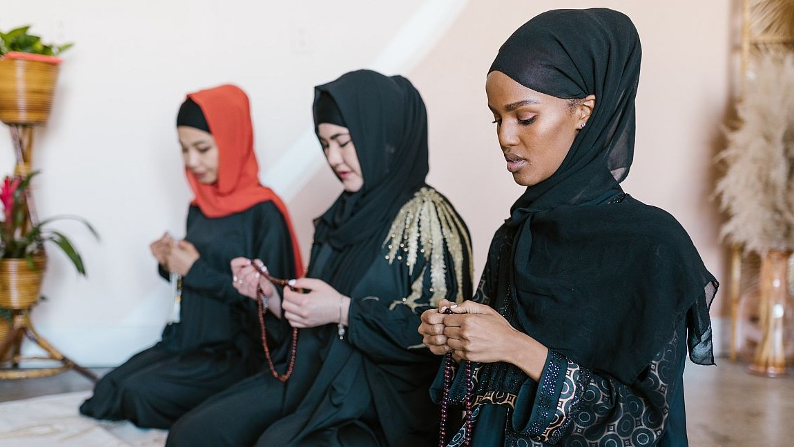 Three Muslim women pray together. Via Pexels
