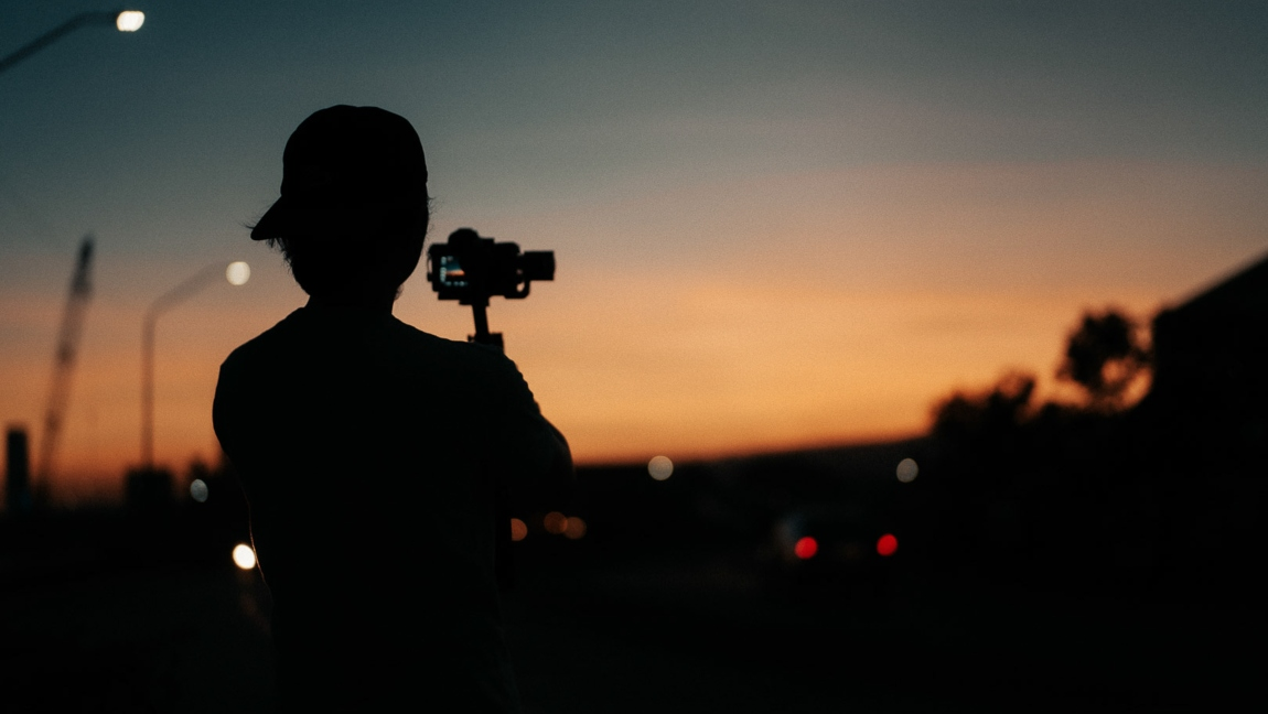A person films a sunset on a video camera
