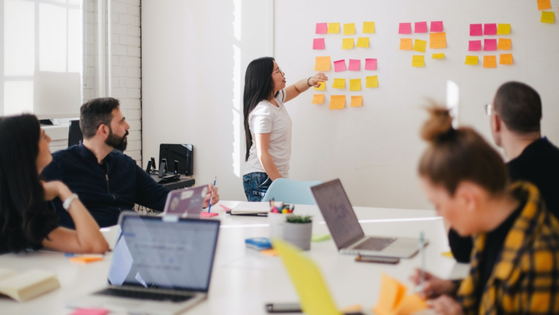 A group of people sit around a table while a woman stands in front of a wall of sticky notes