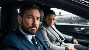 Steve Arnott and Chloe Bishop, played by Martin Compston and Shalom Brune-Franklin, sit in a car during a stakeout.