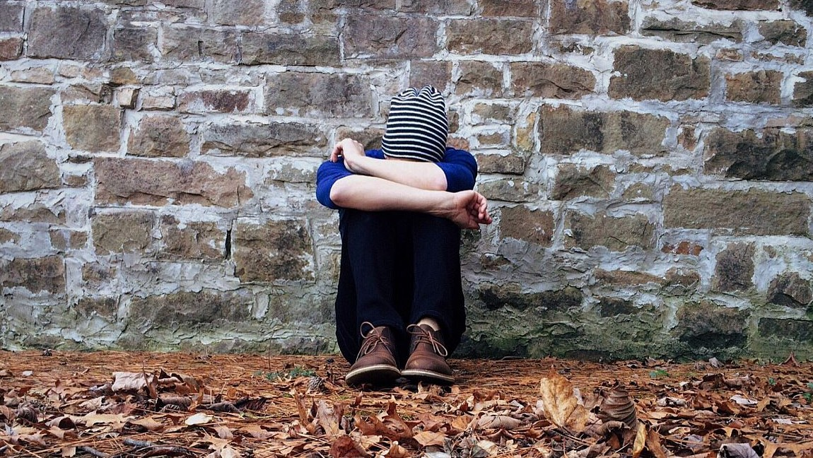 A person sits with their head in their hands while leaning against a wall