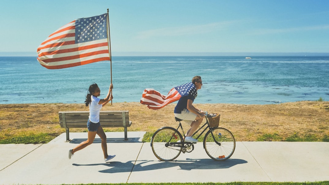 [Image description: Two people with American flags racing down a sidewalk by the water.] Via Unsplash