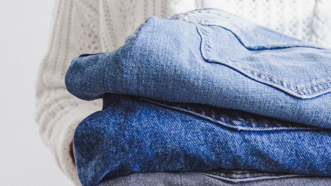 A person holds a stack of jeans