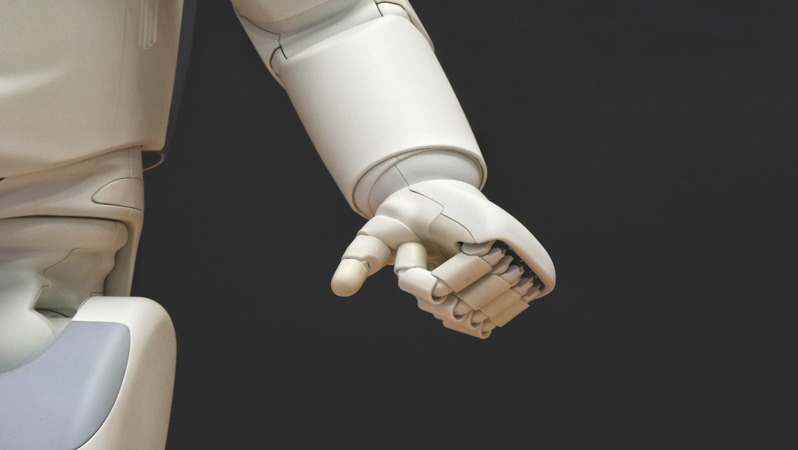 A close-up shot of the torso, arm, and hand of a robot