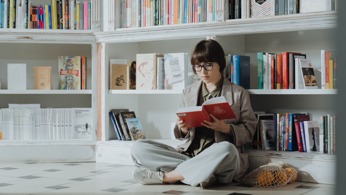 [Image description: Woman reading while sitting down in front of a book case.] Via Pexels