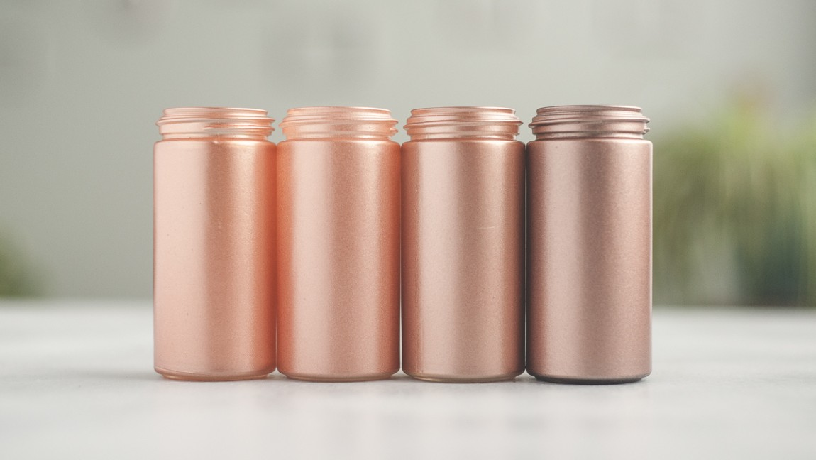 Four bottles painted in various shades of rose gold.