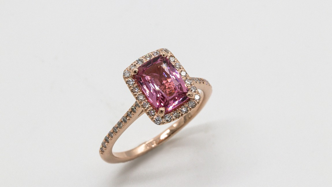 A rose gold ring with a large pink gem surrounded by smaller clear gems.