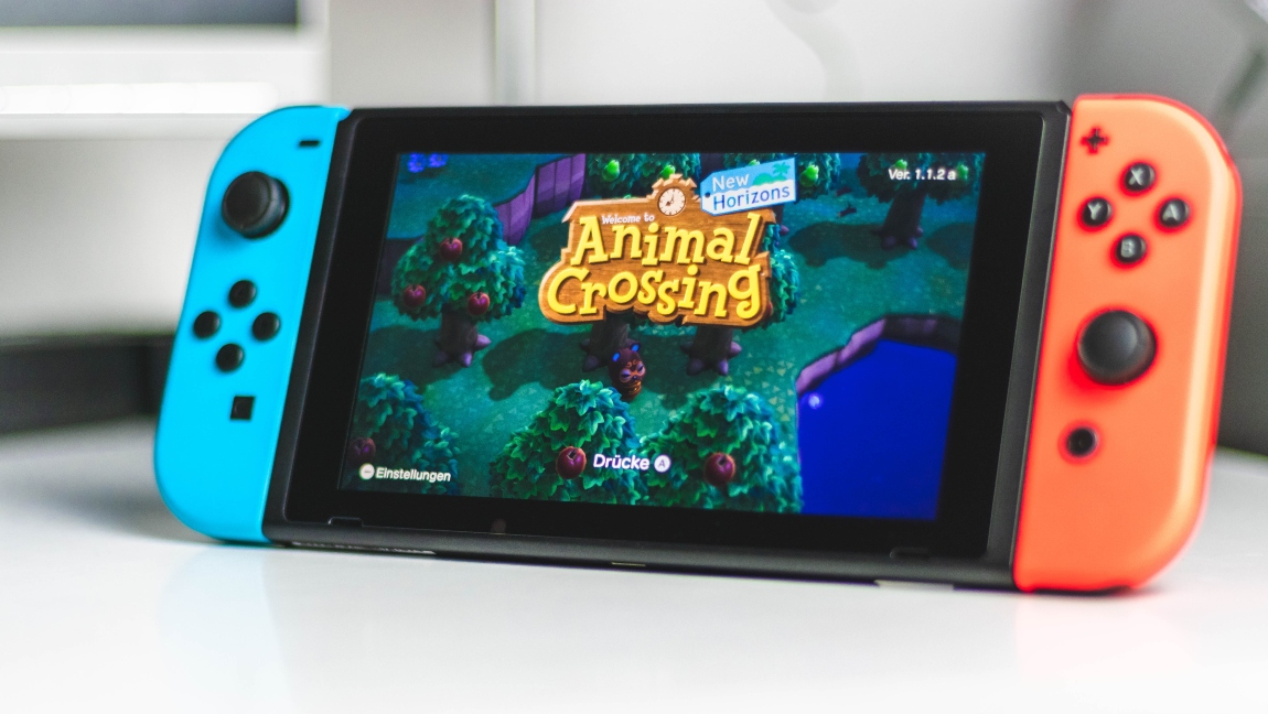 A photo of a Nintendo Switch Lite with the game Animal Crossing on its screen