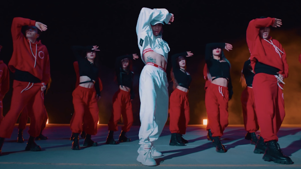"""A still from Taemin's latest music video for """"Advice"""" in which he's wearing a white track suit with a matching Supreme set"""