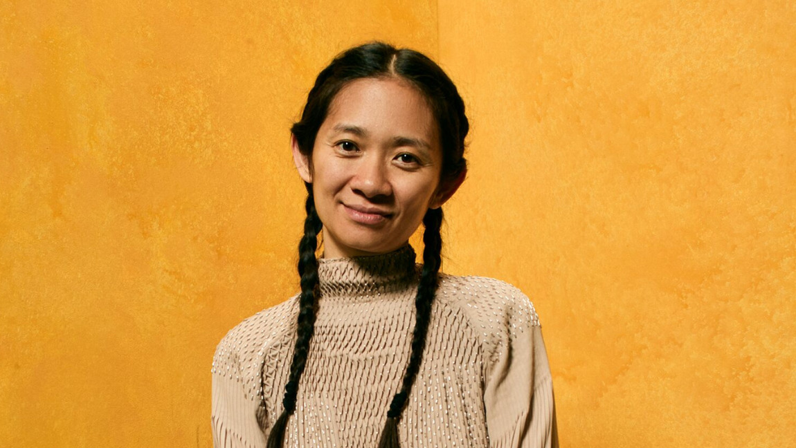 Chloe Zhao sits in front of a yellow background