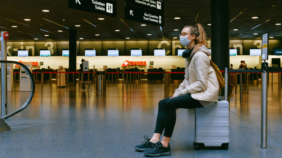A woman wearing a mask sits on her luggage waiting in an airport.