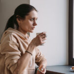 A woman drinks coffee while looking out of the window.