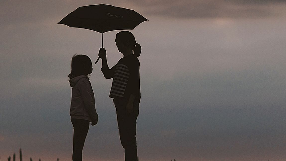 A woman and her daughter stand under an umbrella