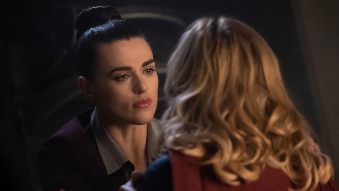[Image Description: Kara looks at Lena seriously while she has her back to the camera and is wearing the Supergirl costume] Via CW