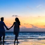 A couple holds hands while walking on a beach at sunset