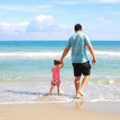 [Image description: A photo of a father holding his daughter's hand, walking on the beach.] Via Pexels
