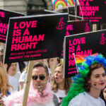 """[Image description: Gay pride marchers with signs that say """"love is a human right"""".] Via Unsplash"""