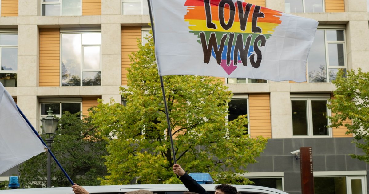 """[Image description: People marching with a flag that says """"Love wins"""".] Via Unsplash"""
