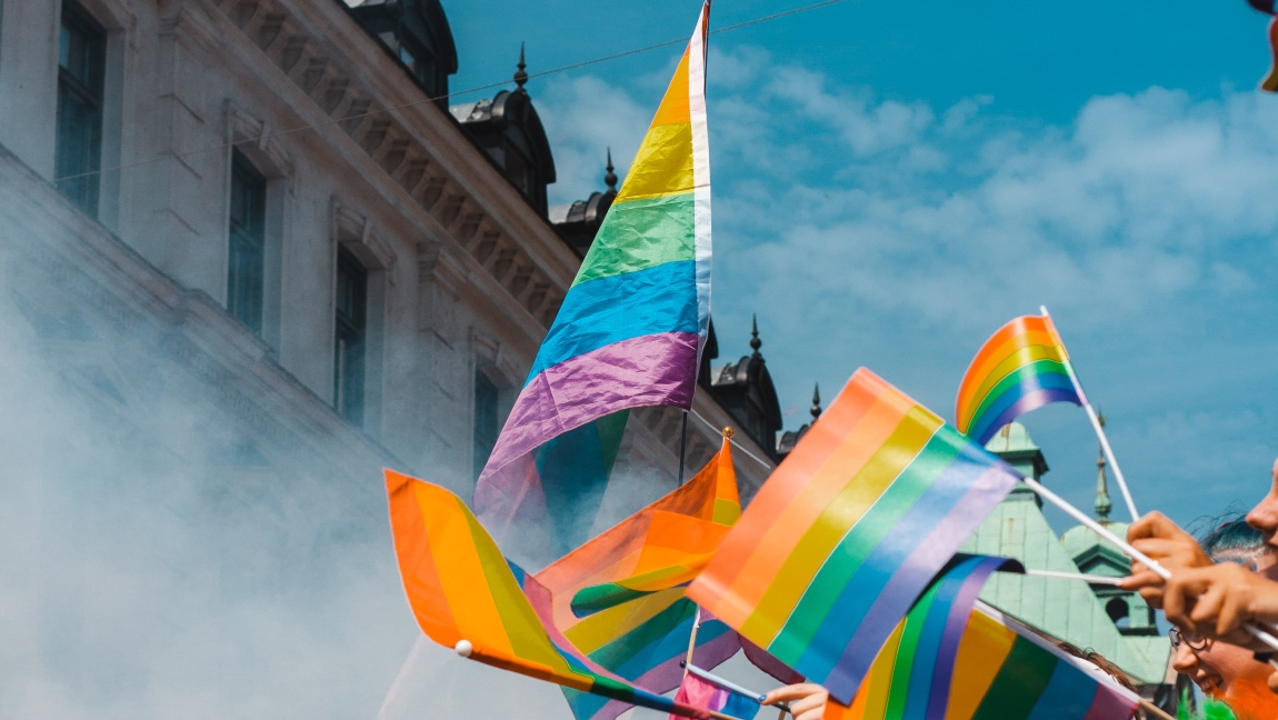 Multiple rainbow flags waved at a Pride celebration