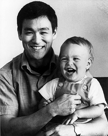 Bruce Lee with his son, Brandon Lee as an infant. Via Wikimedia Commons