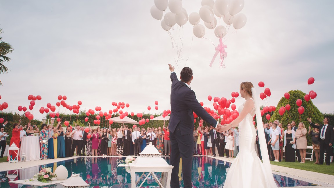 A man in a suit and a woman in a white dress celebrate in front of a pool with multicolored balloons.